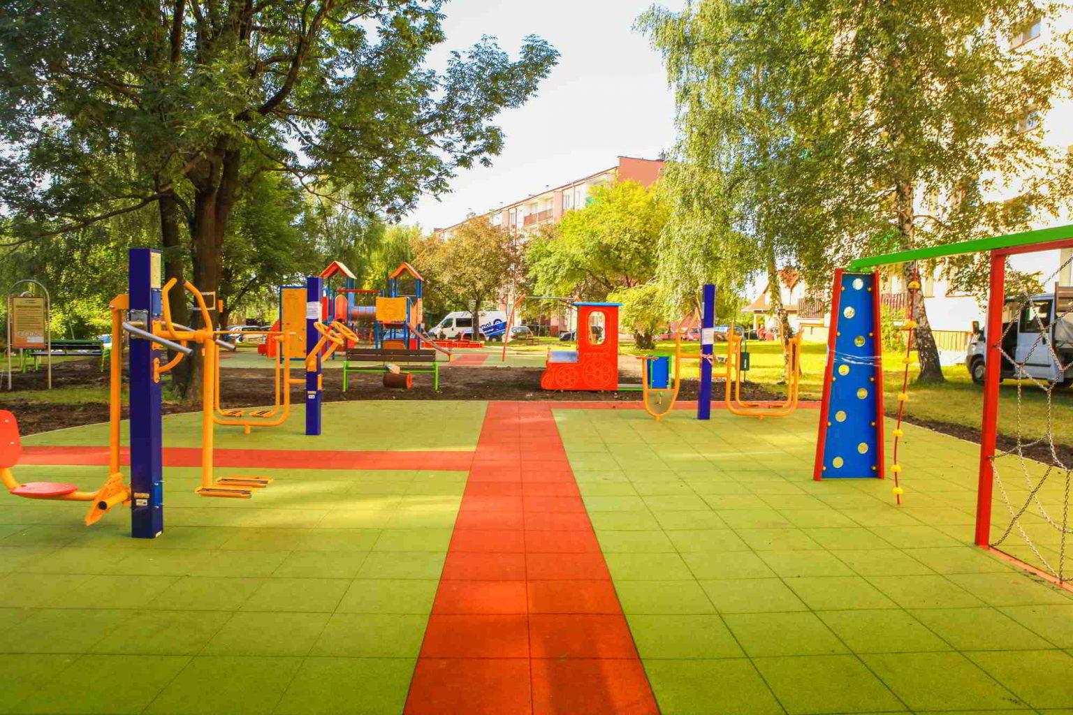 Plac zabaw i siłownia plenerowa z nawierzchnią z płyt gumowych.