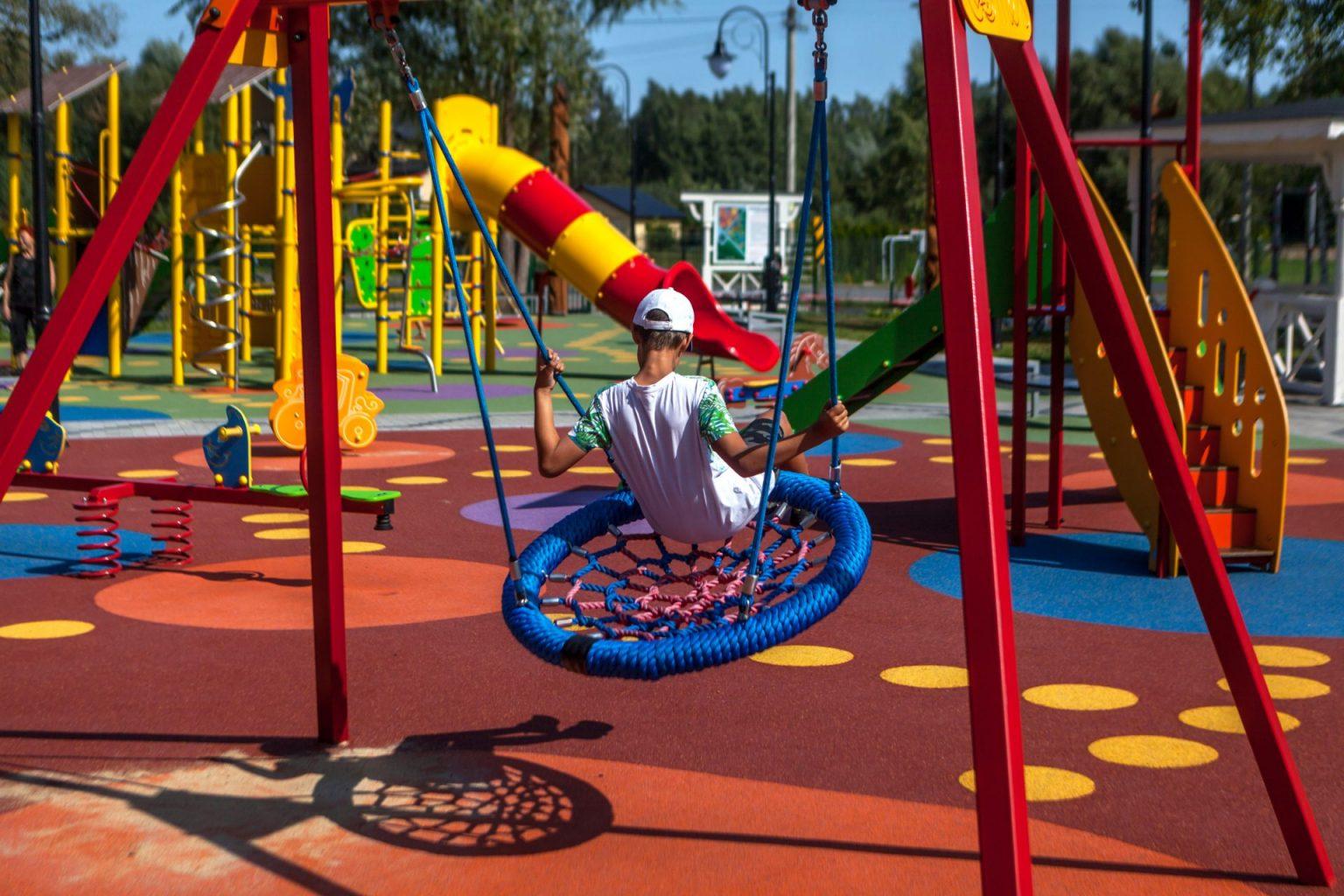 Chłopiec bawi się na placu zabaw. Plac zabaw ma piękną nawierzchnię wylewaną z gumy.